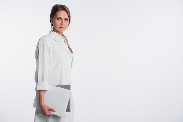 ペーパーおよびラップトップを白で隔離される女医。