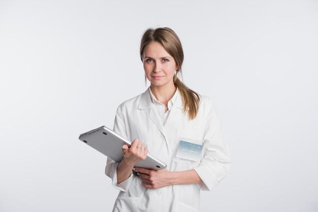 論文とラップトップ、白で隔離される女性医師