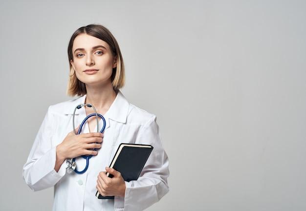 手に聴診器と医療用ガウンのドキュメントを持つ女医