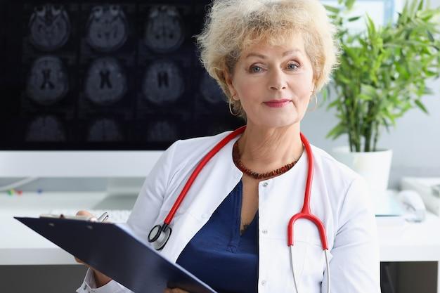 그녀의 손에 의료 문서와 함께 앉아 그녀의 목에 청진기를 가진 여자 의사