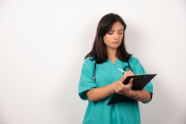 クリップボードに聴診器を書いている女医。