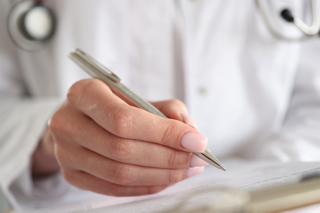 Woman doctor writes patient data into documents with pen