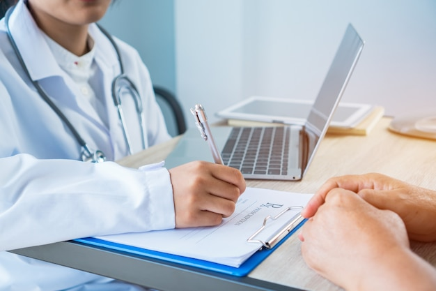 Woman doctor writing prescription clipboard with record information paper