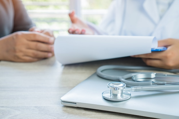 Woman doctor writing prescription clipboard with record information patient listening