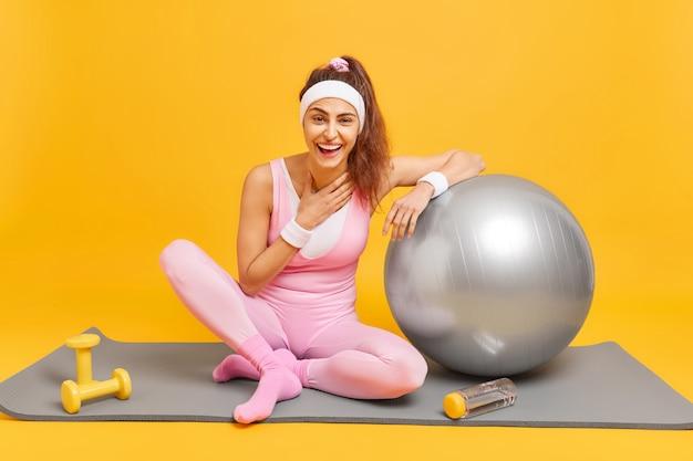 Женщина делает аэробные упражнения на коврике, использует фитбол и пьет воду, счастливо смеется, одетая в спортивную одежду