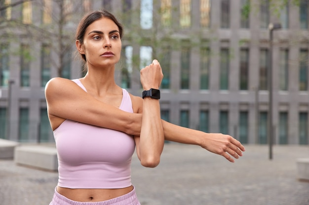 Woman does arm stretching has determined expression warms up before training wears smartwatch cropped top poses near modern building focused into distance