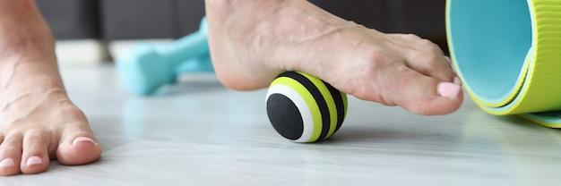 여자는 발 결함과 평평한 발을 교정하기 위해 공으로 운동을 한다