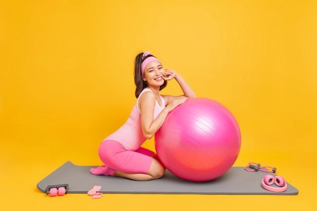 女性はアクティブウェアに身を包んだフィットネスボールで運動します健康的なアクティブなライフスタイルは黄色に分離されたスポーツ用品を使用します
