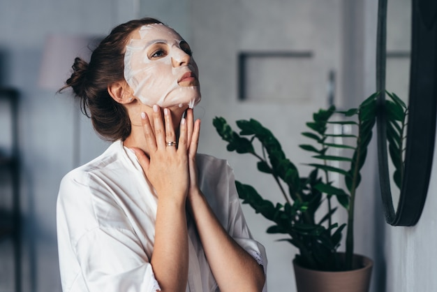 여자는 집에서 얼굴 회춘 치료를합니다.
