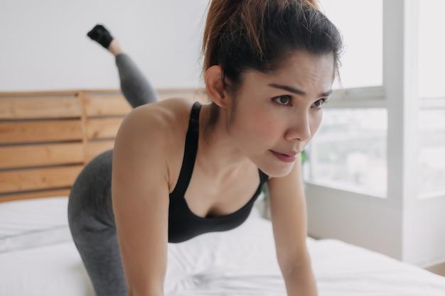 Женщина делает тренировку для ягодичных мышц в своей спальне