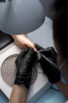 Woman does manicure in beauty salon closeup