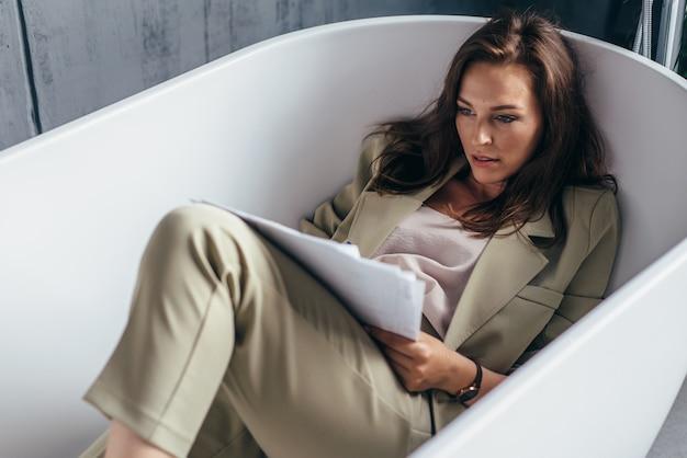 여자는 욕조에 앉아있는 동안 서류를 않습니다.