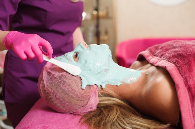 Woman does the procedure in the beauty salon. alginate mask, ultrasonic cleaning. facial skin care. cosmetology procedures without surgery.