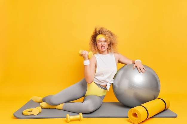여자는 체육관에서 아령과 fitball 기차 필라테스로 스포츠 운동을 한다 이빨은 운동복을 입고 매트에 앉는다