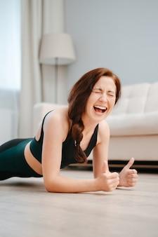 Женщина занимается спортом дома и делает упражнения йоги.