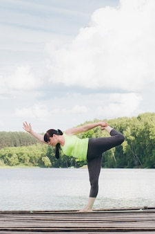 Woman does yoga on the bridge in the summer