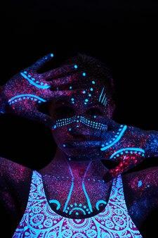 女性はヨガ、手の動き、体のウォームアップを行います。紫外線のアートガールコスモス。全身が色のついた水滴で覆われています。アストラルヨガ。ノイズ、焦点が合っていない