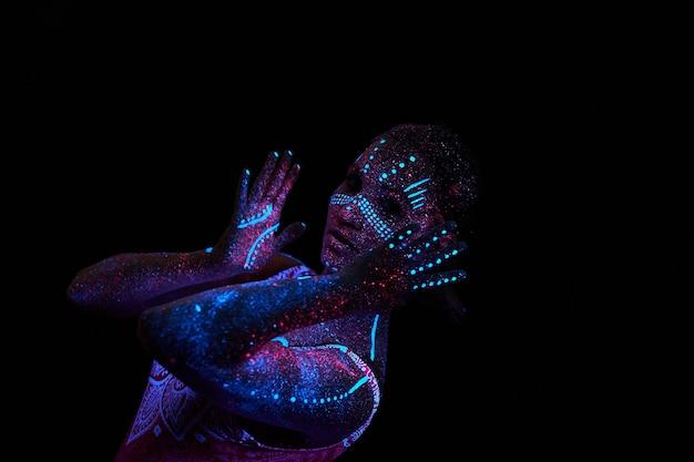 Женщина занимается йогой, движением рук, разминкой тела. космос девушки искусства в ультрафиолете. все тело покрыто цветными капельками. астральная йога. шум, не в фокусе