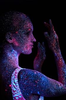 女性はヨガ、手の動き、体のウォームアップを行います。紫外線のアートガールコスモス。全身が色のついた水滴で覆われています。アストラルヨガ