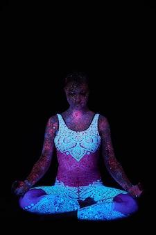 女性はヨガ、手の動き、体のウォームアップを行います。紫外線のアートガールコスモス。全身が色のついた水滴で覆われている