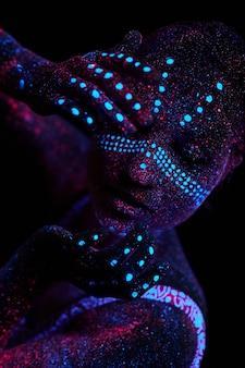 女性はヨガ、手の動き、体のウォームアップをします。紫外光のアートガールコスモス