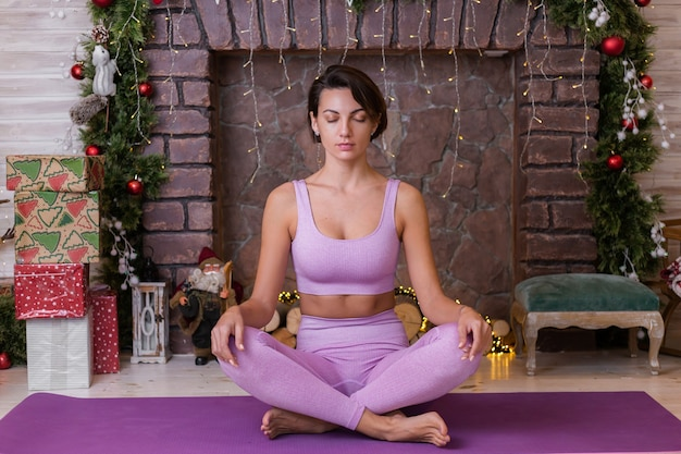 Woman does yoga at home, new year christmas background.