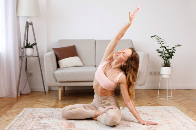 Woman does yoga in the living room