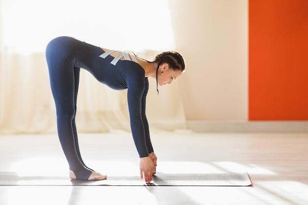 Женщина занимается йогой выполняет упражнения ардха уттанасана, наклонившись вперед на коврике, тренируется в синей спортивной одежде в студии