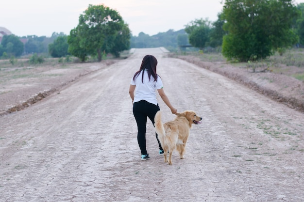 Woman and dog golden walking