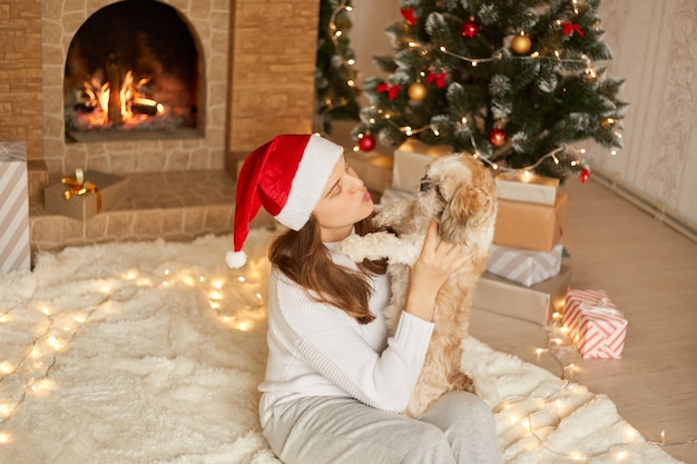 Woman and dog having fun at christmas, sitting on floor on soft carper, lady wants to kiss her dog, posing in cozy living room with x-mas tree and fireplace , girl santa claus hat.
