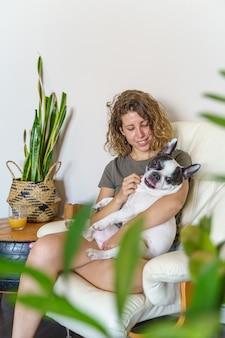 家でブルドッグと女犬愛好家。屋内で植物と犬をくすぐる女性の垂直方向のビュー