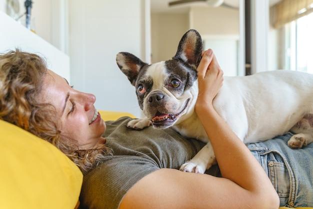 침대에서 불독과 여자 개 애 인입니다. 애완 동물을 가지고 노는 여자의 측면 보기입니다. 실내에서 동물과 함께 하는 라이프 스타일.