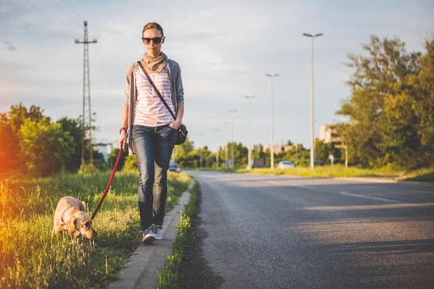 Woman and dog walking by the road