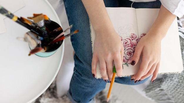 Женщина делает урок рисования со своим телефоном дома