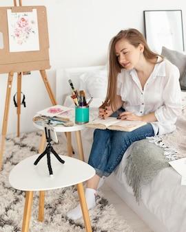 Женщина делает урок рисования со своим телефоном