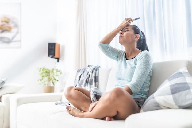 Женщина делает фейспалм после того, как узнала результат теста на беременность.
