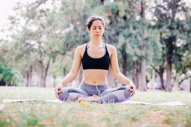 コナサナヨガのポーズを屋外でやっている女性。ヨガの練習に人々のためのピラティス健康的なライフスタイル。屋外でトレーニングし、フィットのコンセプトを維持します。公園で健康な瞑想をしている人々。