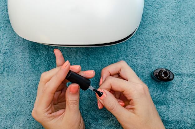 Женщина делает маникюр. окрашивает ногти в коралловый цвет гель-лаком. рядом находится светодиодный светильник для ногтей. концепция ухода за ногтями