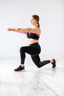 그녀의 핵심 근육을 강화하기 위해 돌진과 앞으로 밀어 넣기 운동 뒤에 파워 밴드를하는 여자