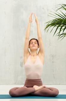 Женщина делает вариацию позы лотоса йоги с вытянутыми над головой руками и безмятежным выражением лица.