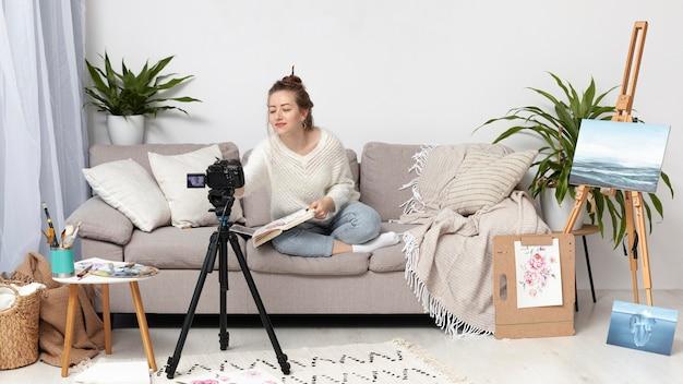 Женщина ведет видеоблог дома со своей камерой