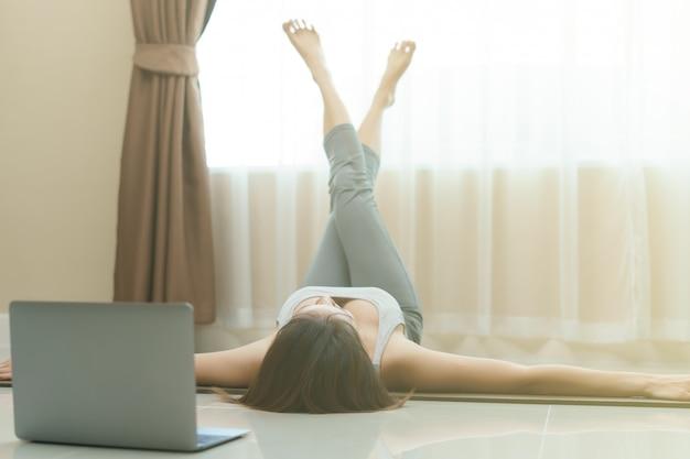 ノートパソコンのビデオクリップで彼女の足のパワーストレッチ運動を行う床に横たわって、トレーニングをしている女性。ストラドルビートエクササイズ