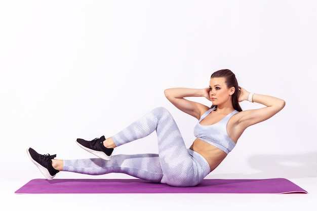 Женщина делает упражнения на скручивание живота на коврике для йоги, накачивает мышцы пресса, ухаживает за телом