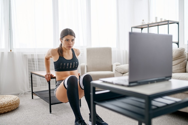 Woman doing abs exercise, online fit training at the laptop