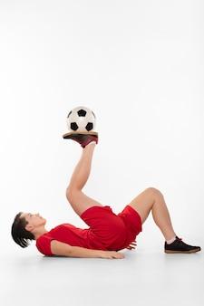 Женщина делает акробатику с футбольным мячом