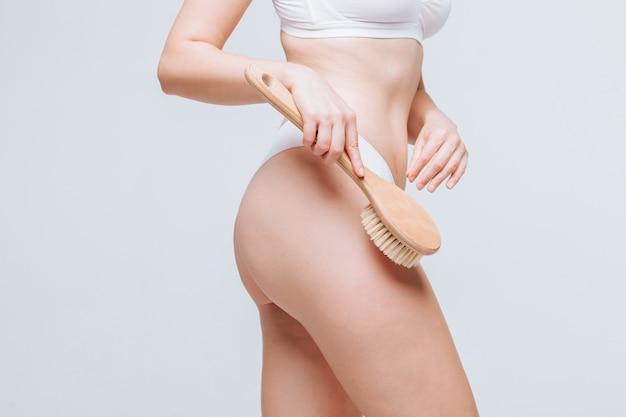 Женщина делает антицеллюлитную массажную щетку