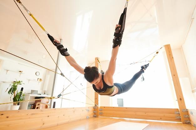 Женщина делает анти-гравитационные упражнения йоги