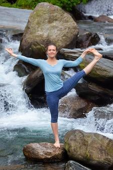 Женщина делает аштанга виньяса йога асаны на открытом воздухе у водопада