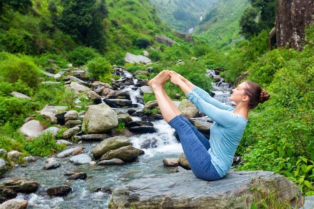 Женщина делает аштанга виньяса йога асаны на открытом воздухе