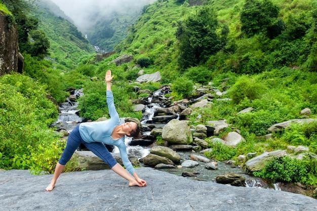 Женщина выполняет аштанга виньяса йога асана уттхита триконасана